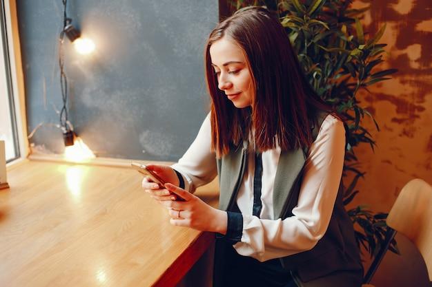 カフェの窓の近くのテーブルに座っている白いブラウスの女の子と電話を保持