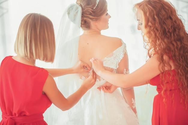 Девушка в белом платье у себя дома. невеста с косметикой. свадьба. подготовка невесты к предстоящей свадьбе.