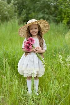 カモミールフィールドで白いドレスを着た女の子。女の子はデイジーと笑顔の花束を抱きしめます。