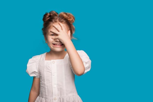 白いドレスを着た女の子が笑顔で手のひらで頭に触れています