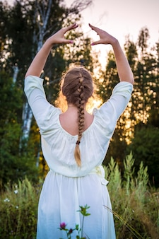하얀 드레스를 입은 소녀는 숲에서 일몰을 바라보며 숨을 쉬고 이완합니다.