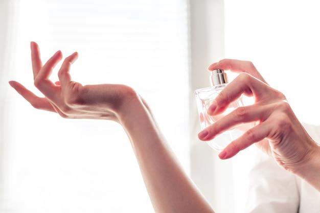 하얀 드레스를 입은 소녀가 손목에 향수를 뿌린다