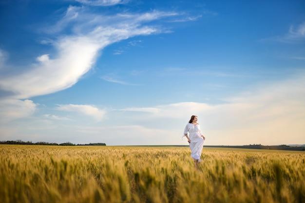 Девушка в белом платье гуляет в пшеничном поле