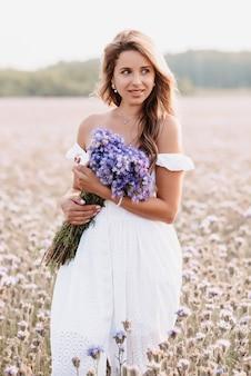 Девушка в белом платье с букетом фиолетовых цветов в поле на природе летом