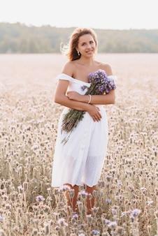 여름에 자연의 필드에 보라색 꽃의 꽃다발과 흰 드레스 소녀