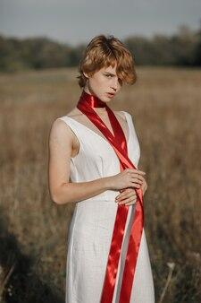 Девушка в белом платье с красной лентой