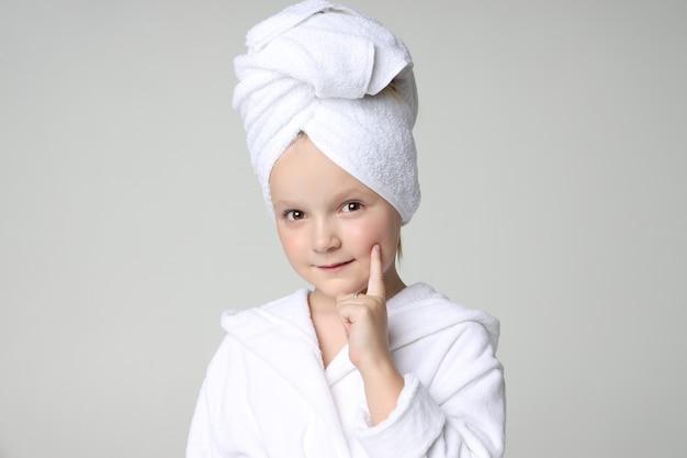 흰 가운에 여자 샤워 후 그녀의 머리를 세척 후 그녀의 머리에 수건. 어린이 화장품 및 스킨 케어, 스파 트리트먼트. 깨끗하고 아름다운 머리카락.