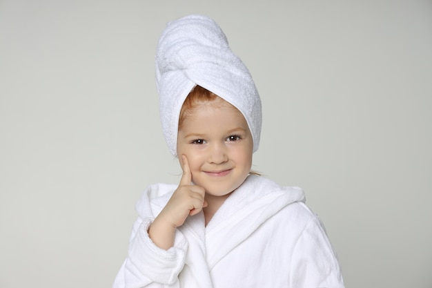 흰 가운을 입은 소녀와 샤워 후 머리에 수건을 두르고 머리카락을 씻습니다. 어린이 화장품 및 스킨 케어, 스파 트리트먼트