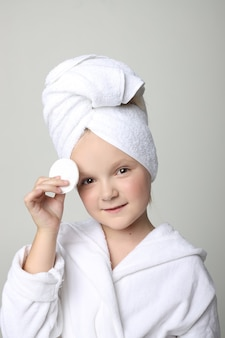 シャワーを浴びて髪を洗った後、白いローブを着て頭にタオルをかぶった女の子。子供用化粧品とスキンケア、スパトリートメント