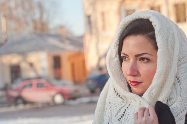 Девушка в белом шарфе на голове. девушка крупным планом. женщина повязывает на голову шарф.