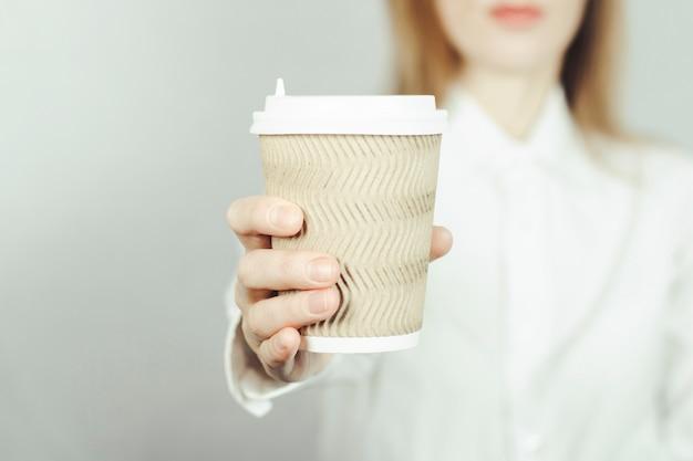 Девушка в белой рубашке держит в руке перед ней бумажный стаканчик кофе или чая. еда на вынос концепции, кафе.