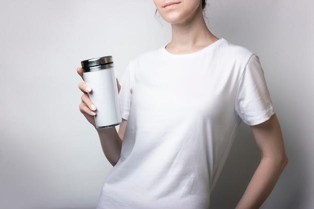 白いtシャツの女の子は、コーヒーとサーモカップを保持しています。ブランディングの場合は空白。モノクロモックアップ