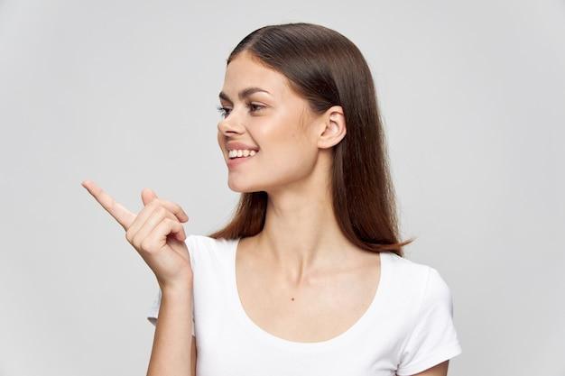 白いtシャツの女の子は指を側に表示し、孤立した笑顔