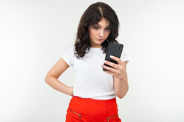 白いtシャツを着た女の子は、コピースペースと白いスタジオの背景にスマートフォンでメッセージをよく読んでいます。