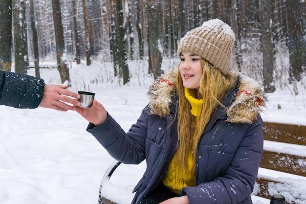 겨울 공원에서 소녀는 그의 친구에게 뜨거운 음료와 함께 머그잔을 전달