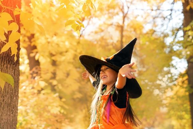 魔女の衣装と黄色の葉を背景に大きな黒い帽子の女の子