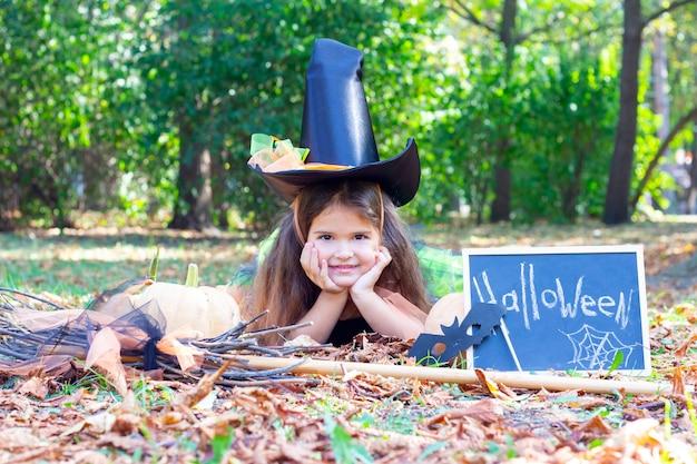 ハロウィーンの休日の魔女の衣装を着た女の子。碑文のあるプラカード:ハロウィーン。魔女の帽子をかぶって草の上に横たわる少女
