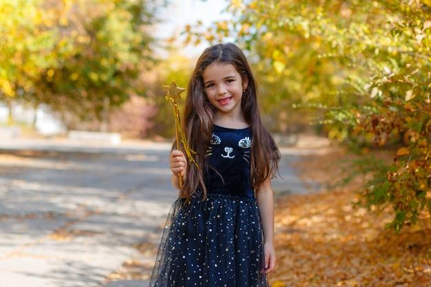 Девушка в костюме ведьмы с волшебной палочкой на хэллоуин в осеннем парке