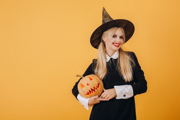 Девушка в шляпе ведьмы с тыквой в руках позирует на фоне желтой стены. фото высокого качества