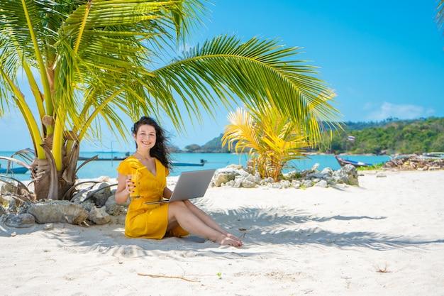 열 대 모래 해변에 노란 드레스에서 소녀는 노트북에서 작동 하 고 신선한 망고를 마신다. 원격 작업, 성공적인 프리랜서. 휴가에 작동합니다.
