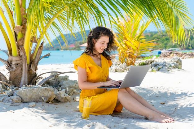 Девушка в желтом платье на тропическом песчаном пляже работает на ноутбуке и пьет свежий манго. удаленная работа, успешный внештатный сотрудник. работает в отпуске.