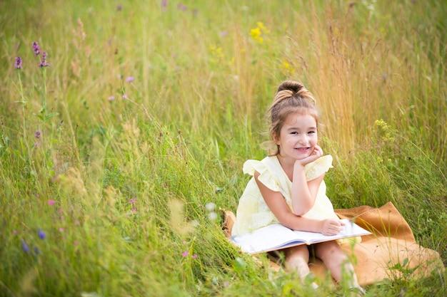 노란색 드레스를 입은 소녀는 필드의 담요에 풀밭에 앉아서 종이 책을 읽습니다. 국제 어린이의 날. 여름철, 어린 시절, 교육 및 오락, 코티지 코어. 공간 복사