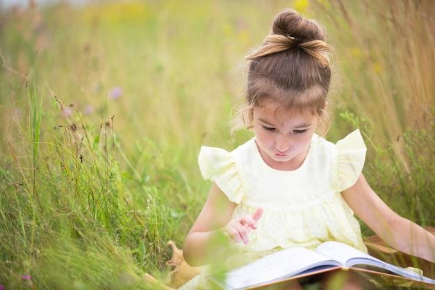 노란 드레스를 입은 소녀가 들판의 담요 위에 풀밭에 앉아 종이책을 읽습니다. 국제 어린이날. 여름 시간, 어린 시절, 교육 및 엔터테인먼트, 코티지 코어. 복사 공간