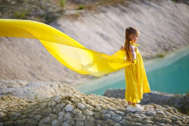 湖の近くの黄色い布に翼を持つ黄色いドレスの女の子