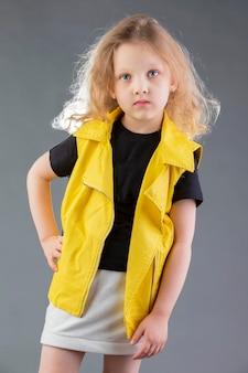 회색 배경에 노란색 재킷을 입은 소녀 5세 소녀 아이를 위한 모델 테스트