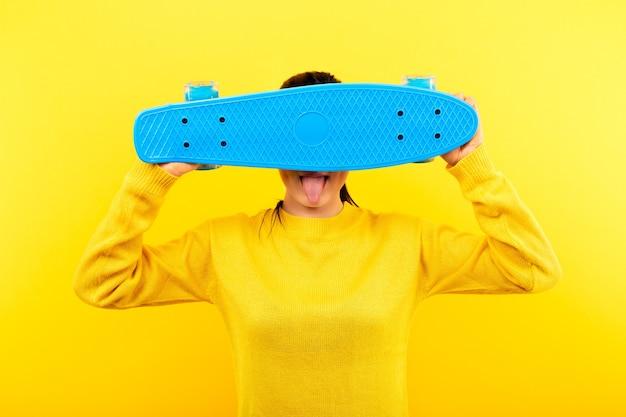 黄色いプルオーバーの女の子が青いスケートボードで顔を覆っている