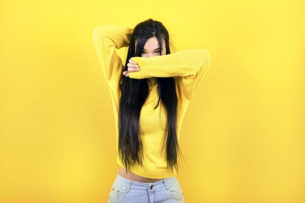 노란색 스웨터를 입은 소녀가 노란색 벽에 그녀의 얼굴을가립니다.