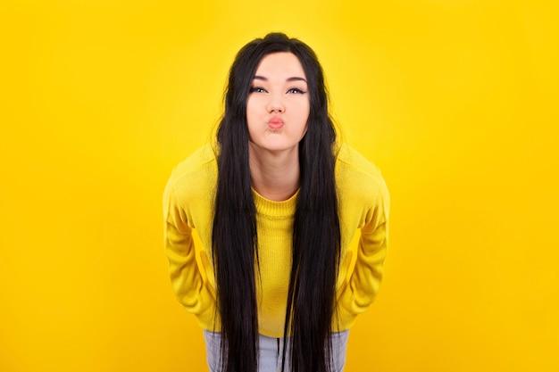 노란색 스웨터를 입은 소녀, 찡그린 얼굴로 뺨과 입술이 부풀어 오른다.