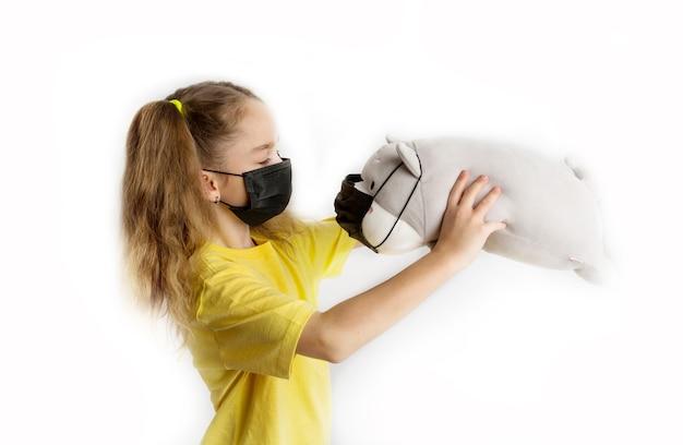 Девушка в желтой футболке и черной маске covid19 на белом фоне с игрушками в маске. фото высокого качества