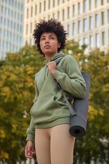 フィットネストレーニングを受けたためにジムから戻ってきたアクティブウェアの女の子は、緑の木々や都市の高層ビルに対してポーズの外でヨガを練習するためにマットを運びます