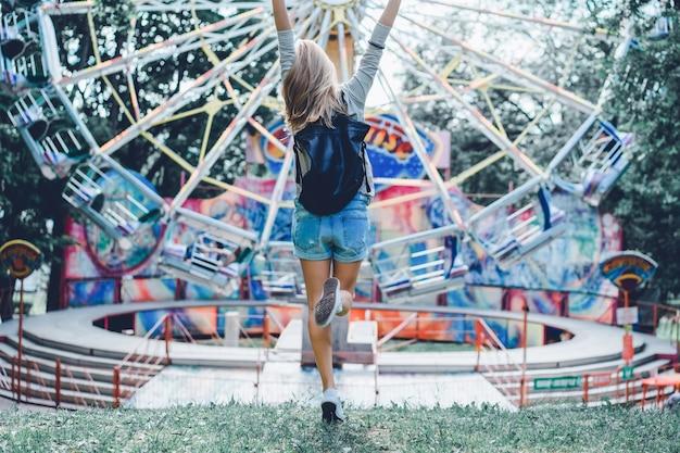 Девушка в парке развлечений на фоне карусели