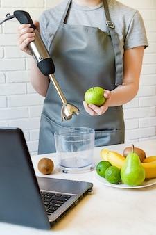 エプロンの女の子はミキサーとリンゴを持っています。インターネットのレシピでフルーツスムージーを作る。
