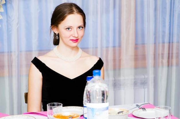 휴일 테이블에 대 한 이브닝 드레스 소녀