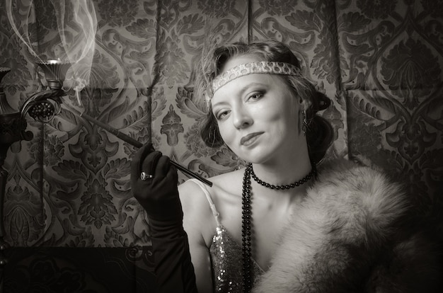 タバコのマウスピースとイブニングドレスの女の子。セピア調のレトロなスタイルのスタジオポートレート