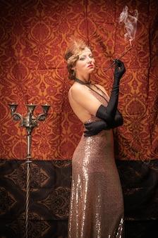 담배와 이브닝 드레스에 소녀입니다. 스튜디오 복고 스타일 사진