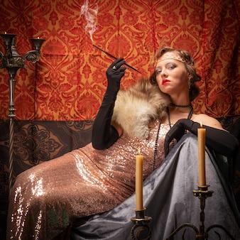 タバコとイブニングドレスの女の子。スタジオレトロスタイルの写真