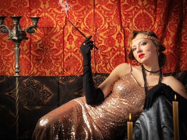 タバコとイブニングドレスの女の子。スタジオレトロスタイルの写真 Premium写真