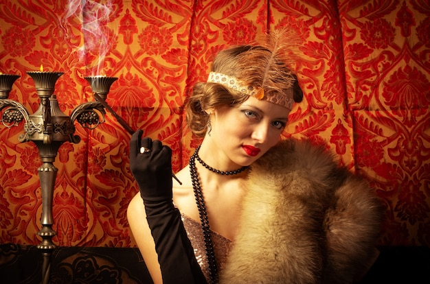담배와 이브닝 드레스에 소녀입니다. 스튜디오 복고 스타일 사진 프리미엄 사진