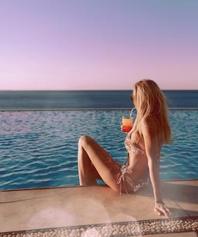그녀의 손에 칵테일을 들고 값비싼 황금 수영복을 입은 소녀가 수영장 가장자리에 앉아 있다