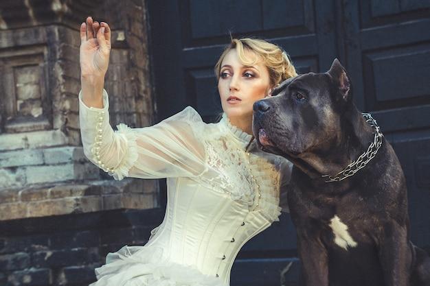 프릴과 큰 어두운 개가있는 오래된 드레스 소녀