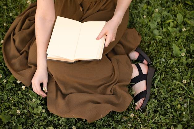 Девушка в оливковом платье держит книгу с пустой страницей в руках, сидя на зеленой траве