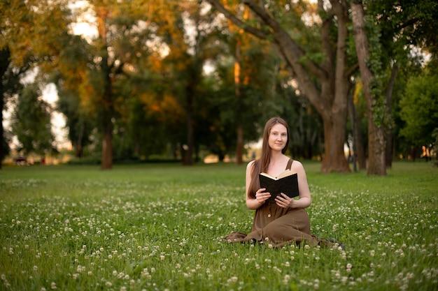 オリーブのドレスを着た女の子が公園の緑の芝生に座って本を読む
