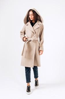 白い背景の上の秋のコートの女の子