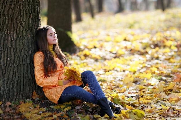 木にオレンジの葉と秋の少女