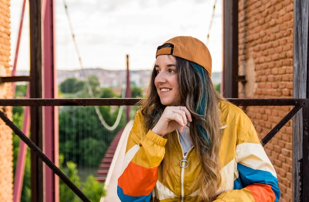 새벽에 빨간 다리를보고 야구 모자와 골드 스포츠 재킷에 소녀. 라이프 스타일 컨셉