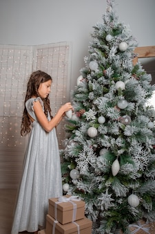 Девушка в красивом платье украшает елку